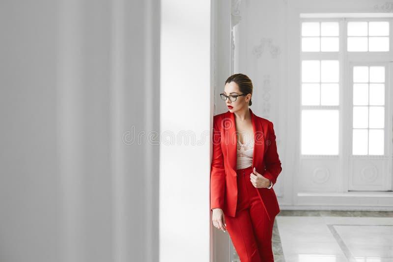 Sexy Geschäftsdame, plus Größenmodellmädchen in den stilvollen Gläsern und in der roten modernen Klage, die nahe dem Fenster am w lizenzfreie stockfotos