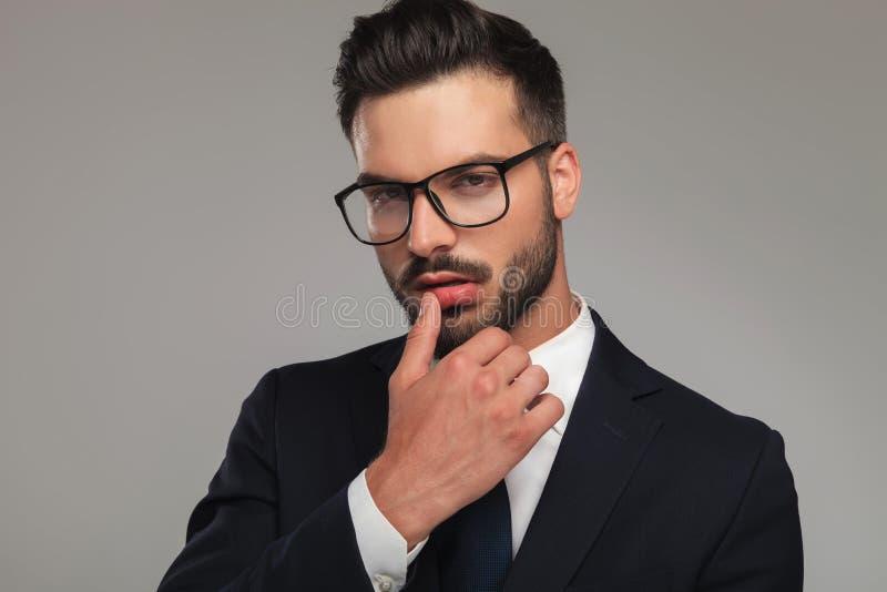 Sexy Geschäftsmann, der mit dem Daumen auf Lippen flirtet lizenzfreie stockfotos
