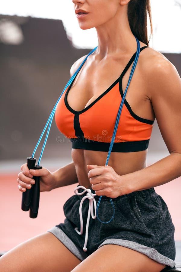 Sexy geschiktheidsvrouw met touwtjespringen, training Mooi atletisch meisje, sportenconcept stock foto