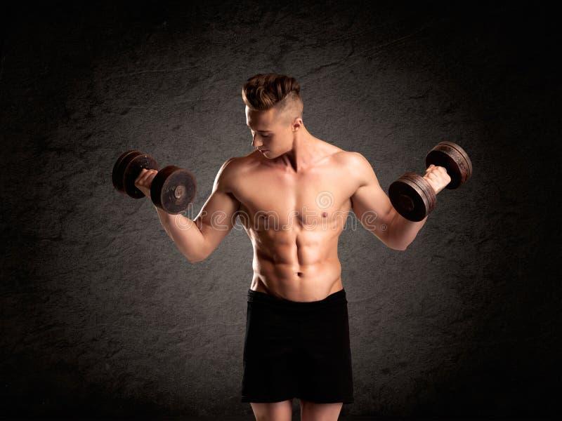 Sexy Gewichtsheberkerl, der Muskeln zeigt stockbild