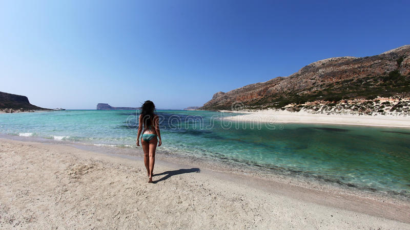 Girl on a beach with turquoise clear waters. A panoramic landscape from Balos Lagoon, Crete, Greece with a looking woman moving towards the crystal clear stock photography