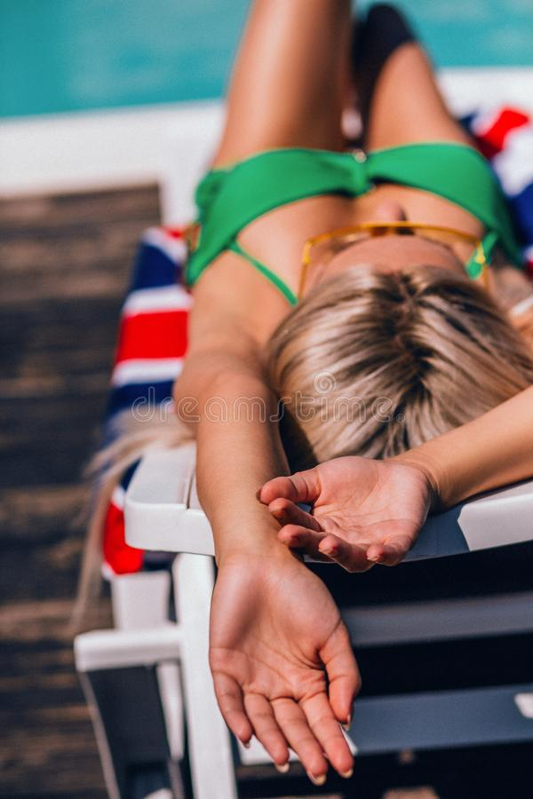 Sexy girl with blond hair in green bathing suit lying and sunbathing on beach royalty free stock images