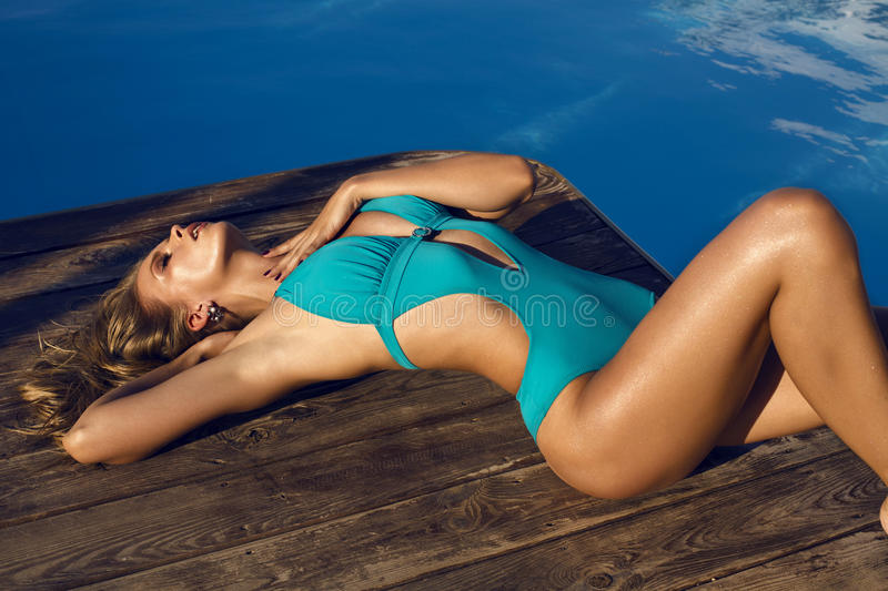 girl in blue swimsuit relaxing beside a swimming pool stock images