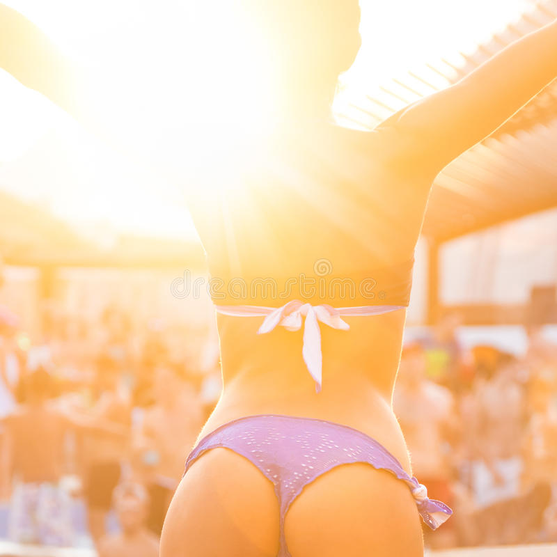 Girl dancing on a beach party. Hot girl wearing brazilian bikini dancing on a beach party event in sunset. Crowd dancing and partying at poolside in background stock photo