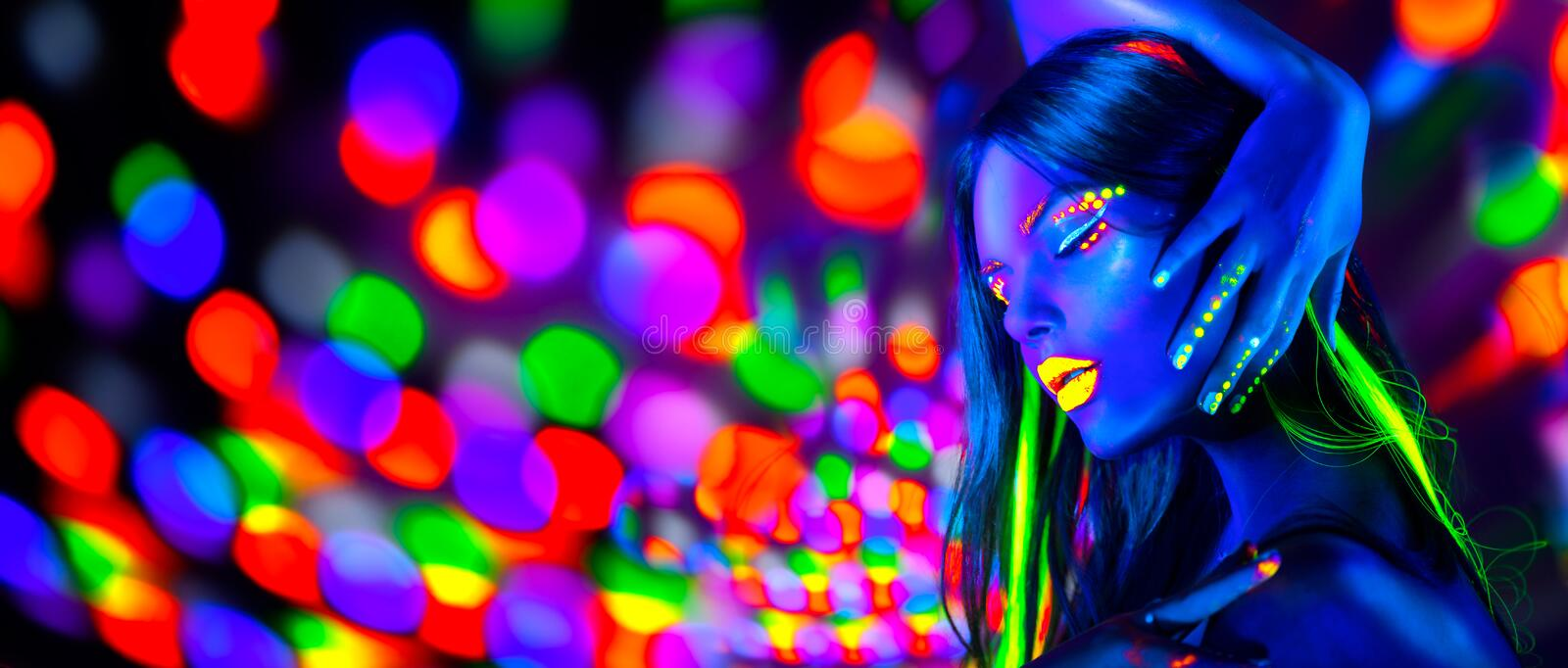 Sexy girl dancing in neon lights. Fashion model woman with fluorescent makeup posing in UV. On bright background stock image