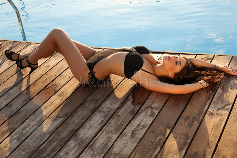 Girl with dark hair in black bikini relaxing on beach. Fashion photo of beautiful girl with dark hair in elegant swimsuit relaxing beside a swimming pool royalty free stock photos