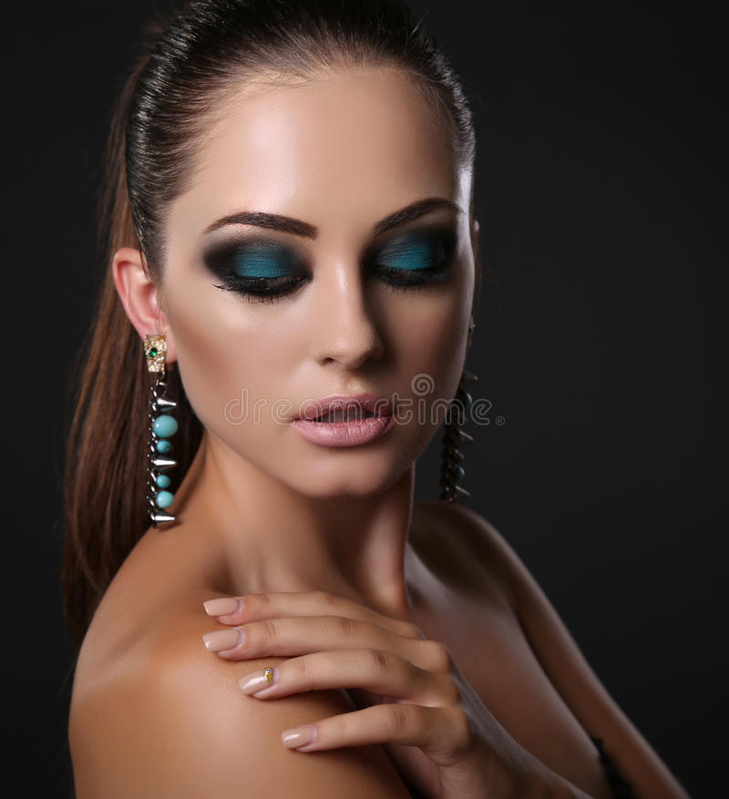 Girl with dark hair and evening makeup with bijou. Fashion studio portrait of beautiful girl with dark hair and evening makeup with bijou stock image