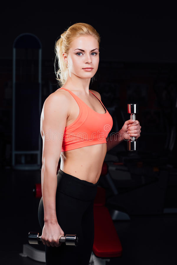girl doing exercises in her arms biceps and triceps. fitness with dumbbells in the gym. royalty free stock images