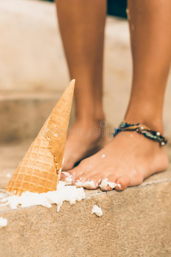 Girl drop her cool icecream on stairs. Close up of tragedy, bad day, negative emotions. Slim lady drop her ice cream in cone on the stone stairs in tropical stock photo