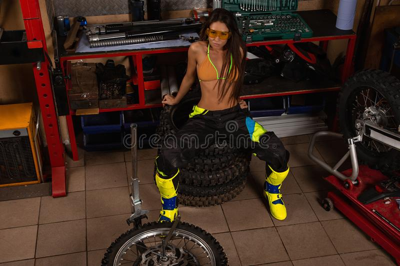 Sexy girl in garage with bike tires royalty free stock images