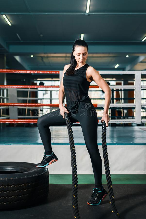 Sexy girl in the gym on the background of the boxing ring. woman holds in her hands the ropes for strength training. There are big car tires next to it royalty free stock images