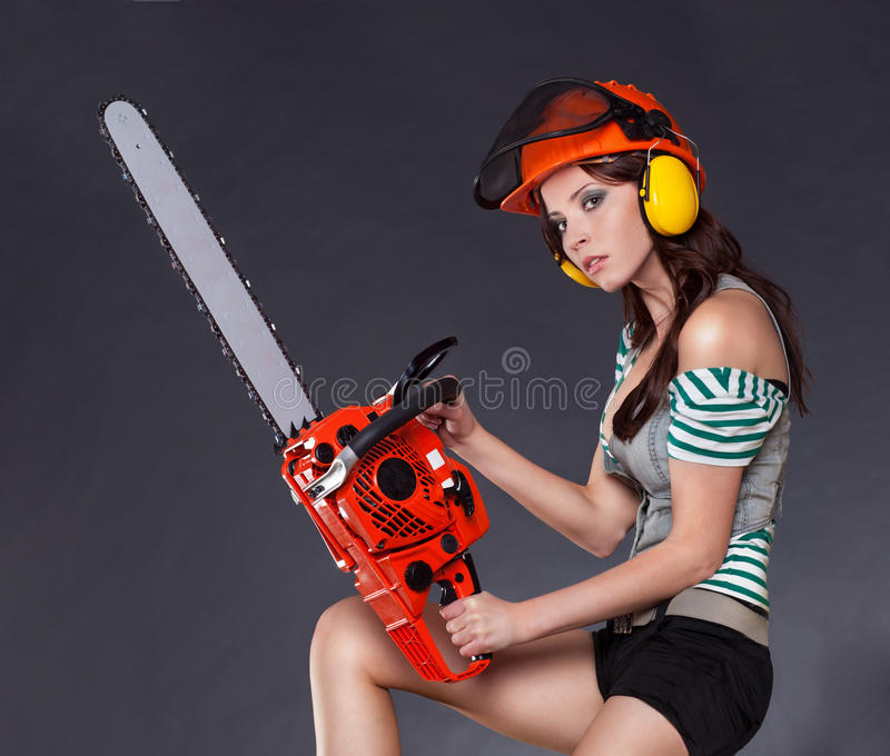 Girl holding a chainsaw stock photo