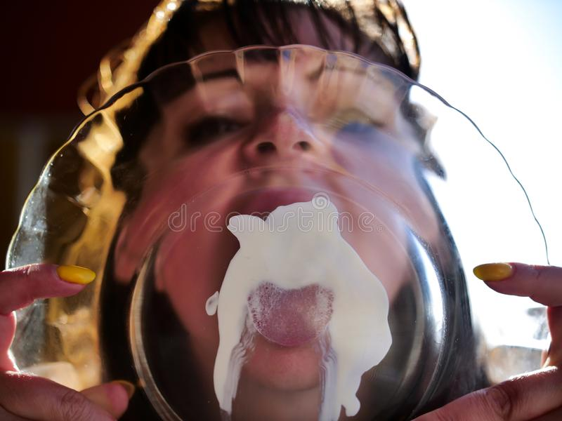 Sexy girl licks a white sauce from a transparent plate royalty free stock image