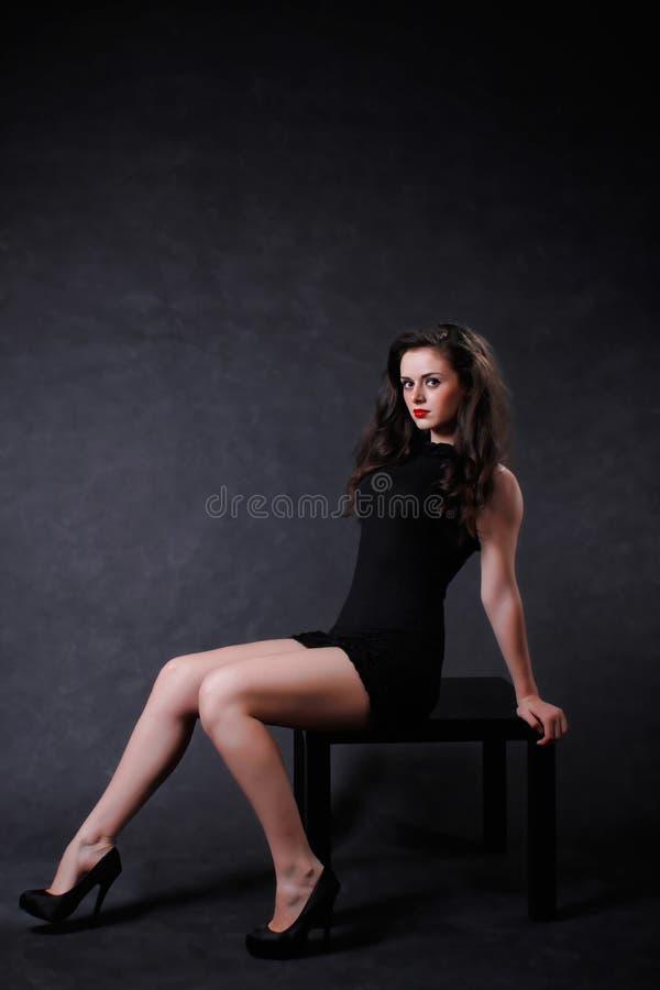 Girl in little black dress. Brunette girl with long legs dressed in the little black dress stock photo
