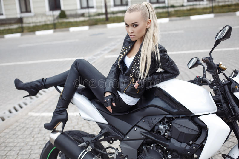 Girl with long blond hair in leather jacket,posing on motorbike. Fashion outdoor photo of beautiful girl with long blond hair in leather jacket,posing on royalty free stock photography