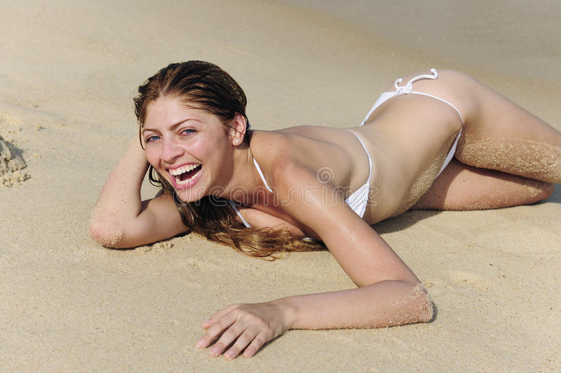 girl lying in the sand on the beach stock images