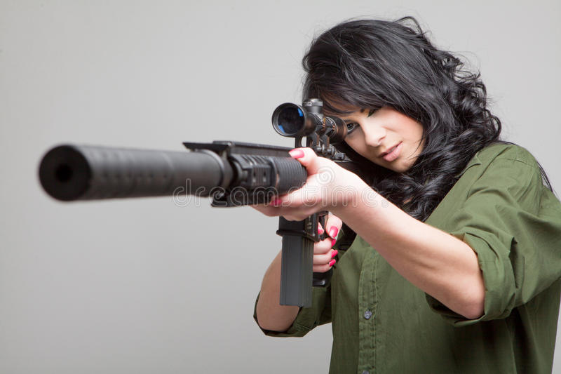 Girl with machine gun. Beautiful girl wearing a green shirt and holding a machine gun aiming on grey background stock photography