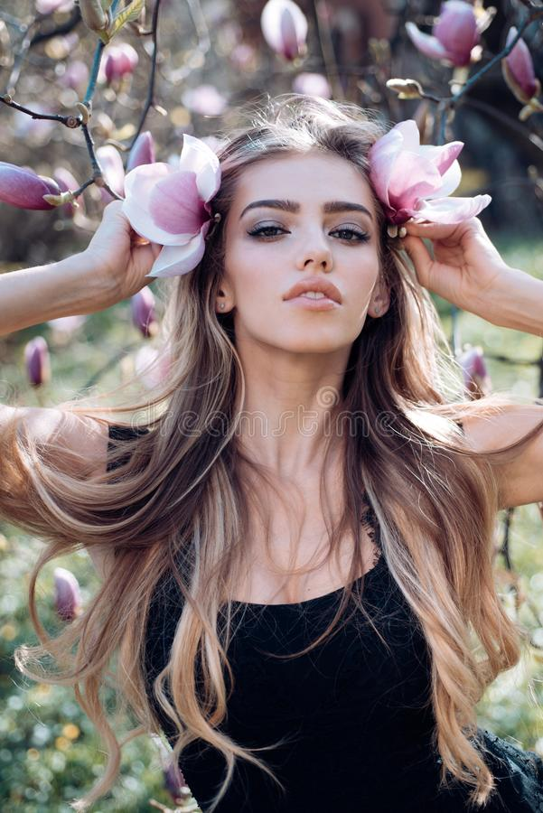 Sexy girl. magnolia blossom. spring. Beauty and fashion. trendy look. Sensual woman. makeup and hair style. long healthy. Hair. happy woman with lush hair stock image