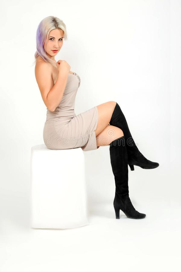 Woman model sits on white cube stock images