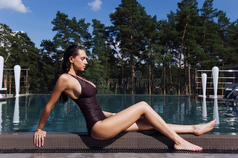 girl with perfect body and long legs sitting near the swimming pool in spa royalty free stock photography