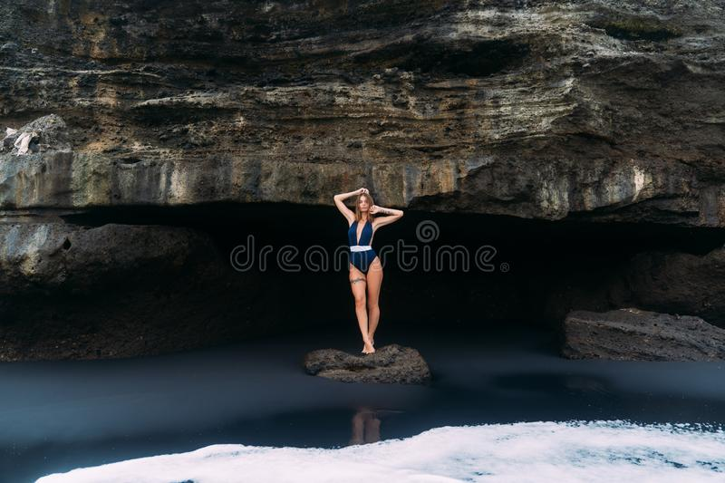 Sexy girl poses in blue swimsuit near cave on black sand beach, concept travel royalty free stock photos