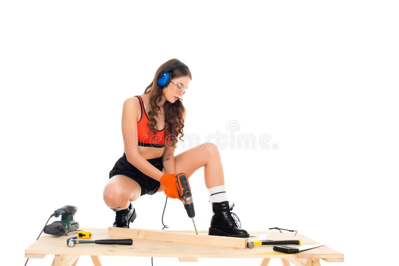 Girl in protective headphones working with electric drill at wooden table with tools,. Isolated on white royalty free stock photo