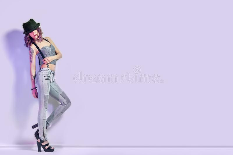 Girl with purple hair and a tattoo on the body posing on purple background, lettering place. Perfect woman in gray jeans. And a t-shirt, bright beautiful makeup stock photos