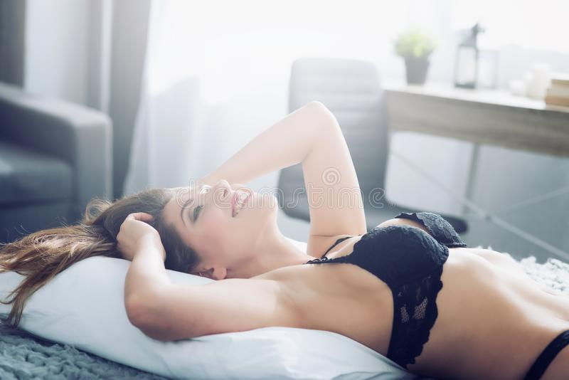 Sexy girl relaxing on the bed during morning. Concept of relax and rest. Sexy brunette girl relaxing on the bed during morning. Concept of relax and rest royalty free stock photography