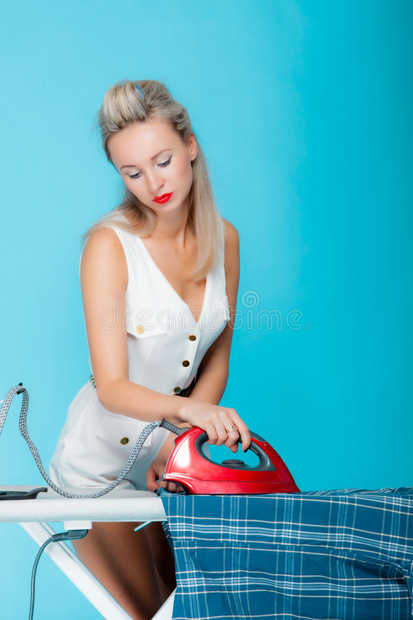 Girl retro style ironing male shirt, woman housewife in domestic role. Traditional sharing household chores. Pin up housework. Vivid blue background stock photo