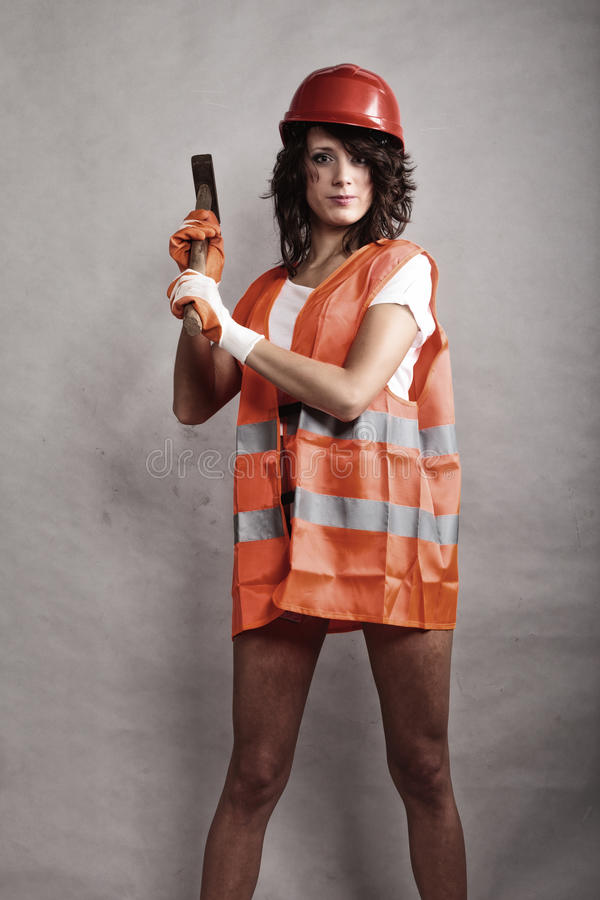 Girl in safety helmet holding hammer tool. Sex equality and feminism. girl in safety helmet orange vest holding hammer tool. Attractive woman working as royalty free stock photography