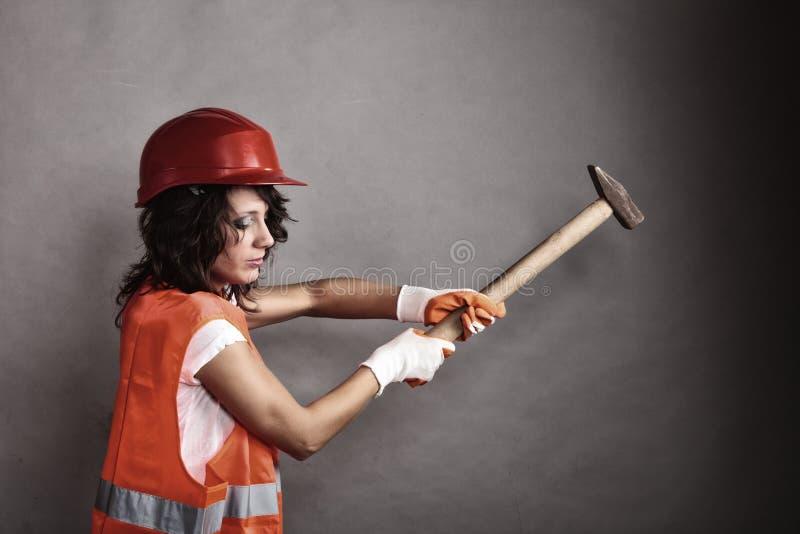 Girl in safety helmet holding hammer tool. Sex equality and feminism. girl in safety helmet orange vest holding hammer tool. Attractive woman working as stock photo
