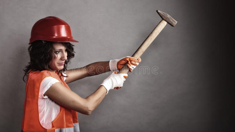 Girl in safety helmet holding hammer tool. Sex equality and feminism. girl in safety helmet orange vest holding hammer tool. Attractive woman working as royalty free stock images