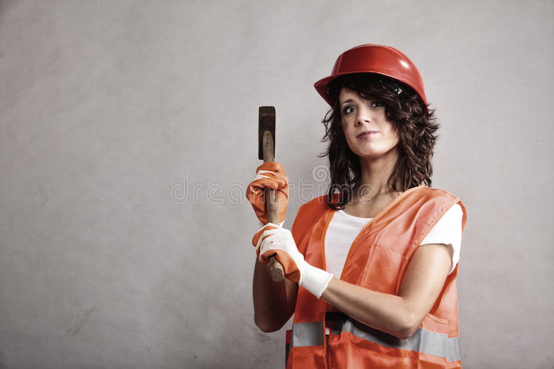 Girl in safety helmet holding hammer tool. Sex equality and feminism. girl in safety helmet orange vest holding hammer tool. Attractive woman working as royalty free stock photos