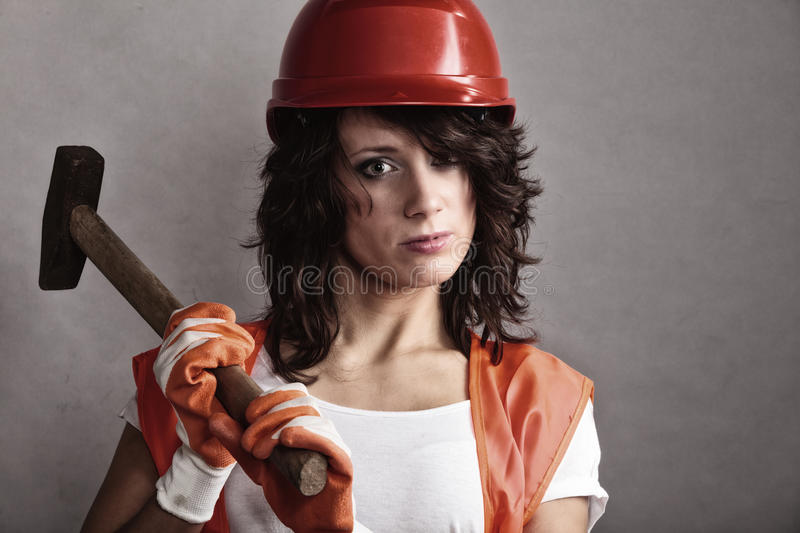 Girl in safety helmet holding hammer tool. Sex equality and feminism. girl in safety helmet orange vest holding hammer tool. Attractive woman working as stock photos