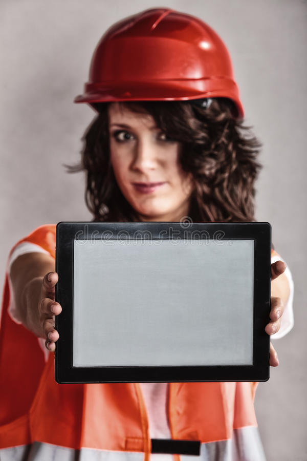 Girl in safety helmet showing tablet. Sex equality and feminism. girl worker in safety helmet and orange vest showing copy space on tablet touchpad royalty free stock images
