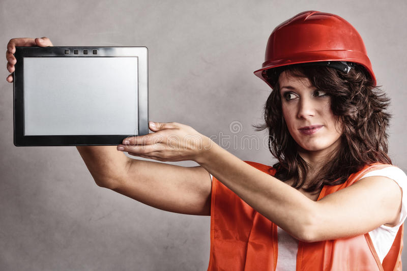 Girl in safety helmet showing tablet. Sex equality and feminism. girl worker in safety helmet and orange vest showing copy space on tablet touchpad stock image