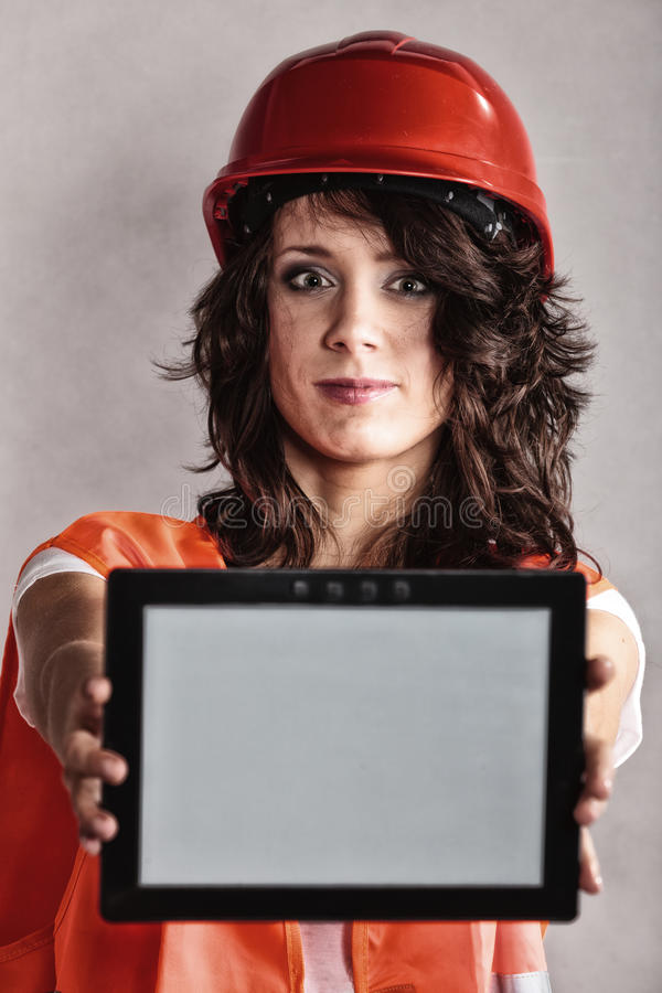 Girl in safety helmet showing tablet. Sex equality and feminism. girl worker in safety helmet and orange vest showing copy space on tablet touchpad royalty free stock photo
