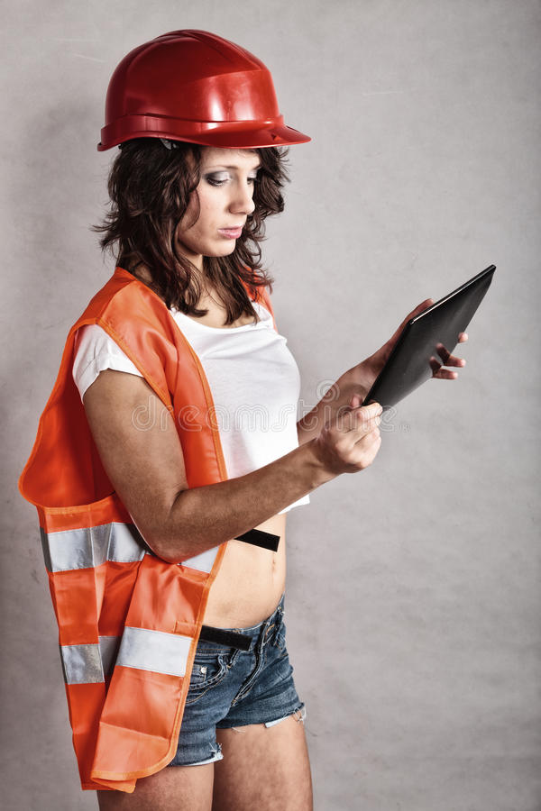 Girl in safety helmet using tablet touchpad. Sex equality and feminism. girl in workwear safety helmet and orange vest using tablet touchpad. Attractive woman as royalty free stock photo