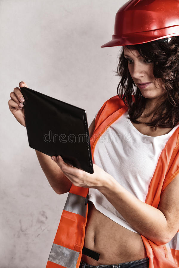 Girl in safety helmet using tablet touchpad. Sex equality and feminism. girl in workwear safety helmet and orange vest using tablet touchpad. Attractive woman as royalty free stock photos