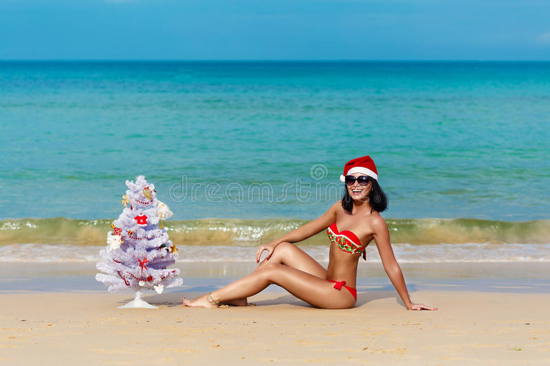 girl Santa in bikini on a beach fir-tree royalty free stock photos