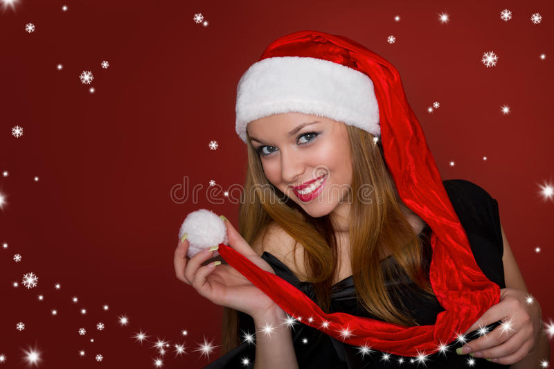 Girl in a santa hat. Beautiful girl in santa hat on red background stock image