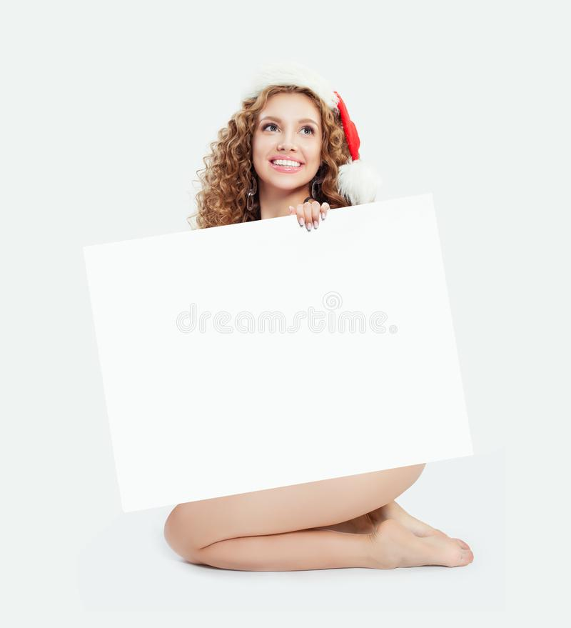 Sexy girl in Santa hat with empty paper banner card on white background royalty free stock photos