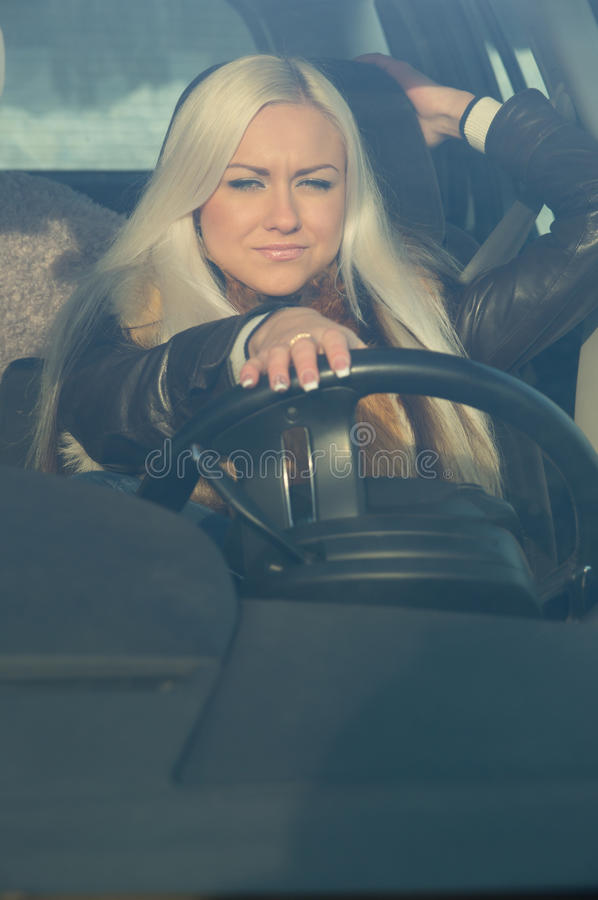 Girl sitting behind the wheel of a car. Winter royalty free stock photos