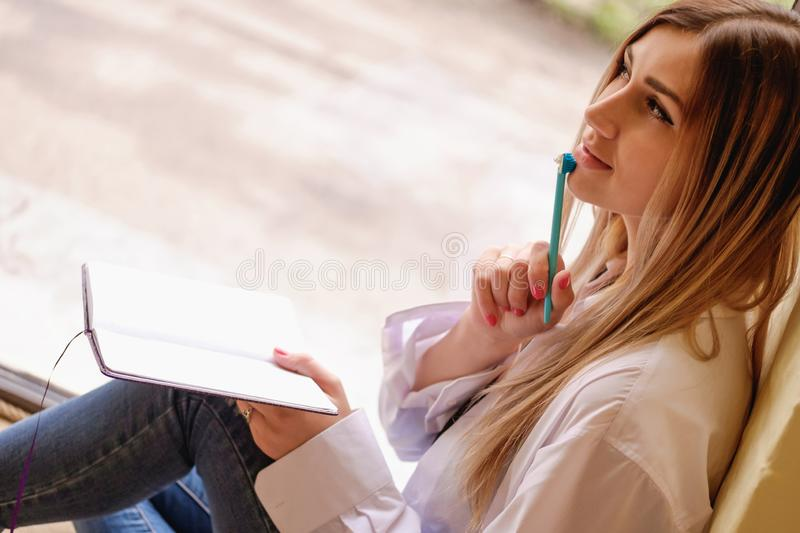 Sexy girl sitting at the table with notebook and pen. single woman in white men`s shirt thinking about something, working. Sexy girl sitting at the table with royalty free stock photos