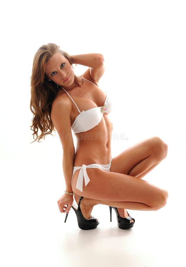 girl squatting in white bikini royalty free stock photography
