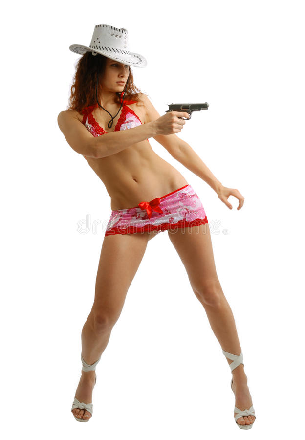 Girl in stetson shooting with gun. Woman is bending to the right and aiming a pistol. Her slender legs on high heels are stood apart. She is wearing white royalty free stock photo