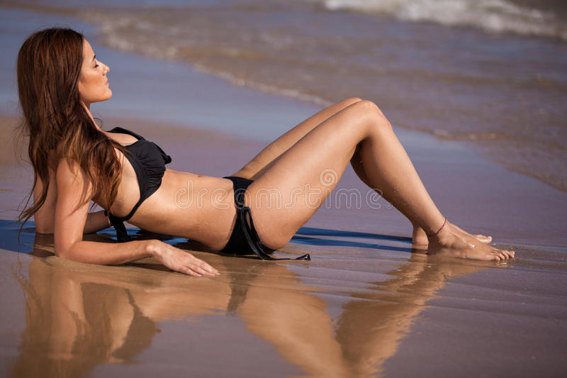 Girl sunbathing at the beach. Beautiful brunette getting a suntan on the beach royalty free stock image