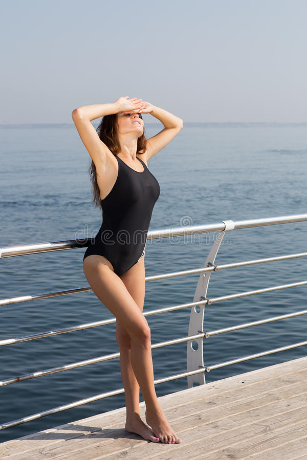 Girl in swimsuit standing on the deck of the yacht royalty free stock photo