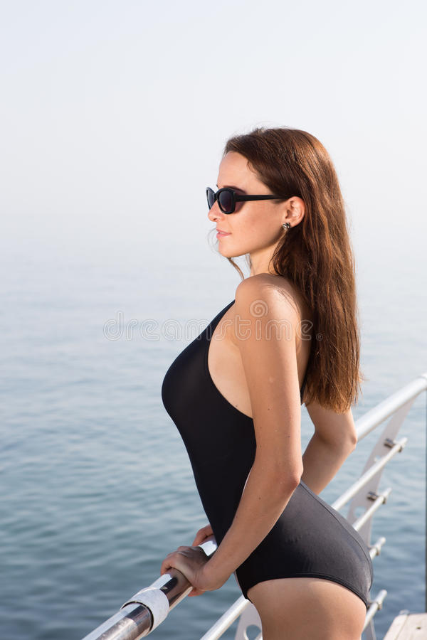 Girl in swimsuit standing on the deck of the yacht royalty free stock images