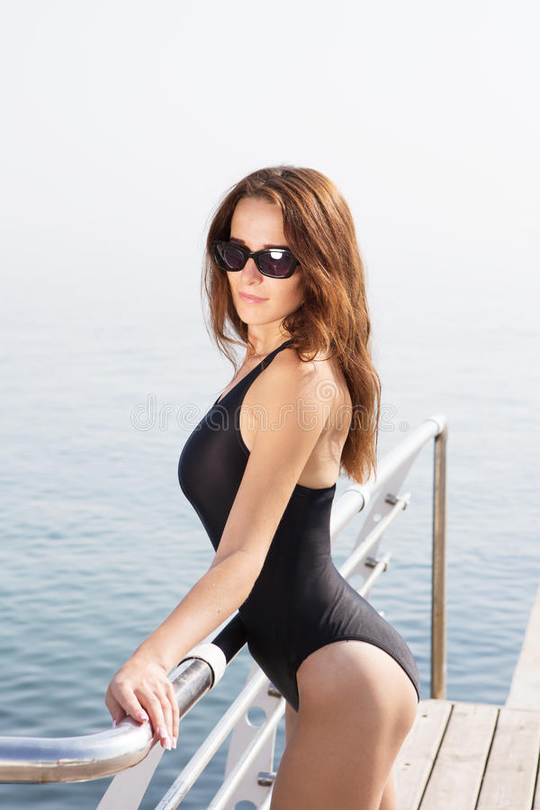 Girl in swimsuit standing on the deck of the yacht stock photos